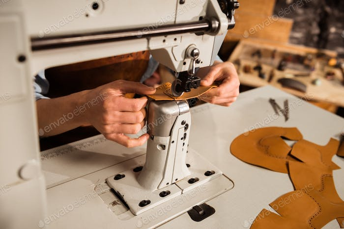 Close up of a shoemaker using sewing machine