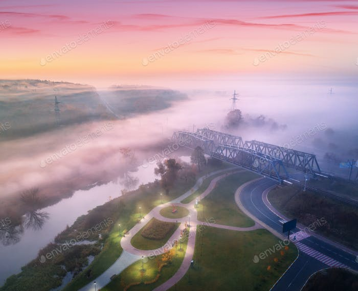 Aerial view of amazing park near river and railway bridge in fog