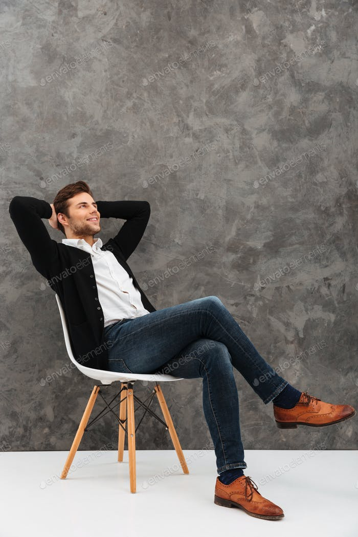 Cheerful young businessman sitting over grey wall