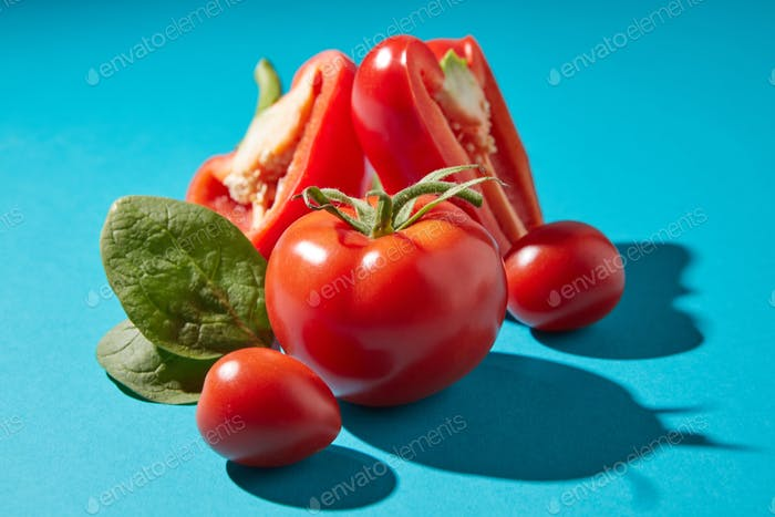 Closeup of organic spinach leaves, peppers and tomatoes on a dark blue background with copy space