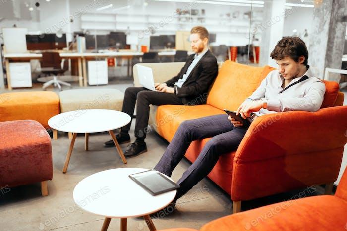 Erfolgreiche Geschäftsleute, die an Geräten arbeiten
