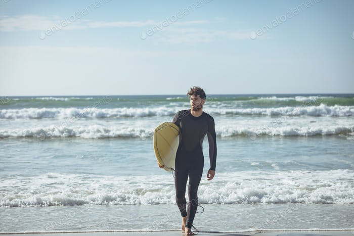 Male surfer with surfboard walking on a beach