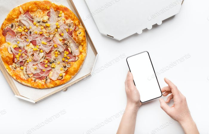 Pizza delivery. Girl holding phone with hot pizza nearby