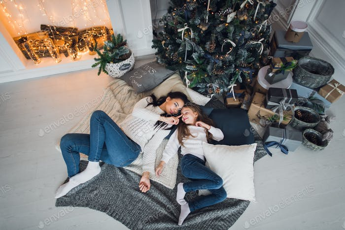 Forever best friends. Top view of happy mom and her daughter wearing jeans and white sweathers lying