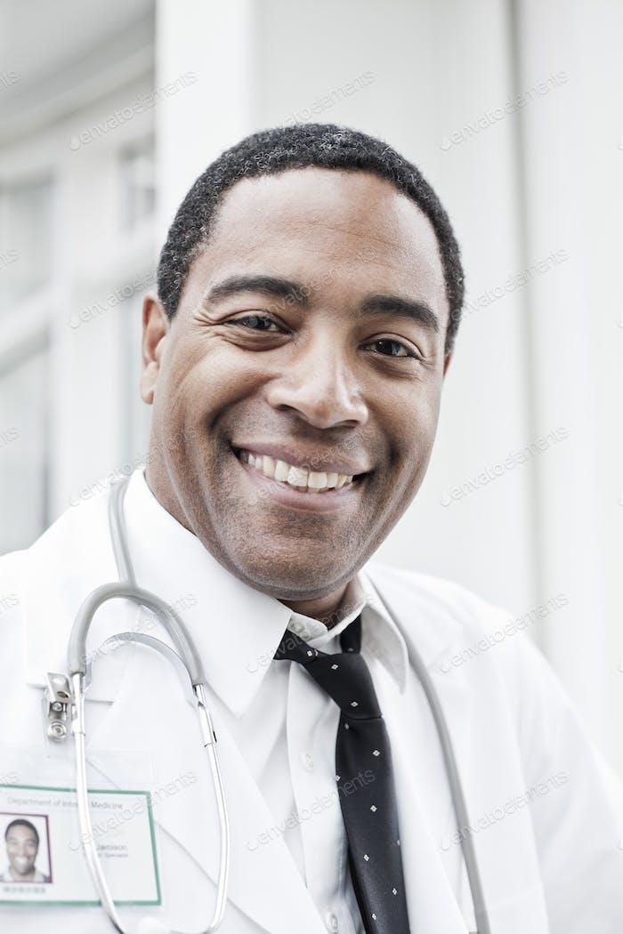 Schwarzer Arzt im Labormantel mit Stethoskop.