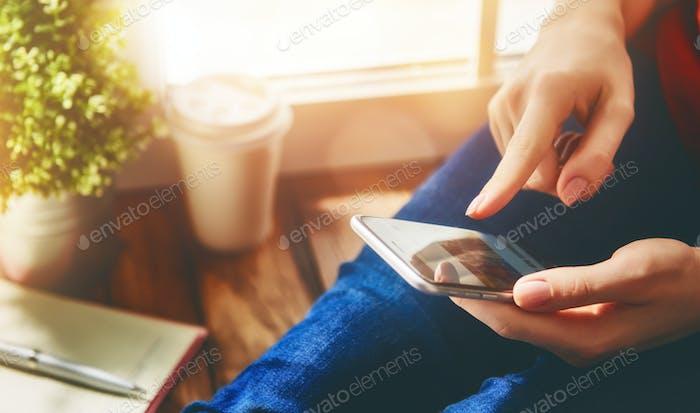 Women is using phone.