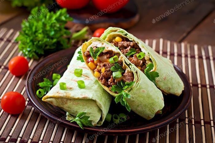 Burritos wickelt mit Hackfleisch und Gemüse auf einem hölzernen Hintergrund