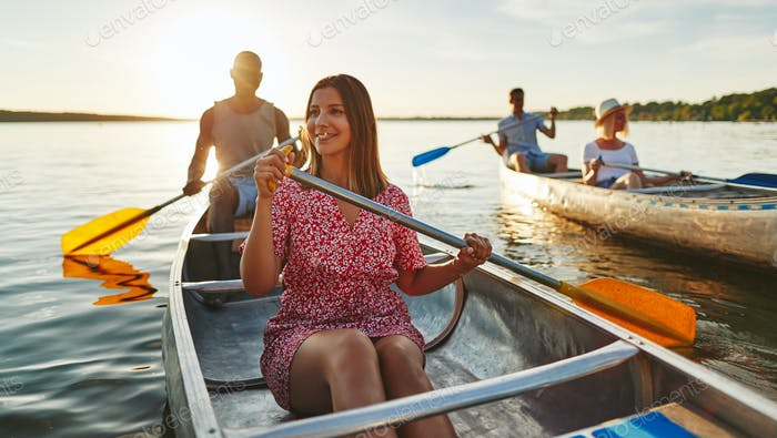 Young woman canoeing with friends on a late summer afternoon