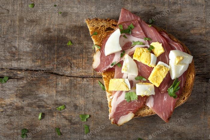 Open sandwich with pork meat, pieces of boiled eggs and chopped parsley