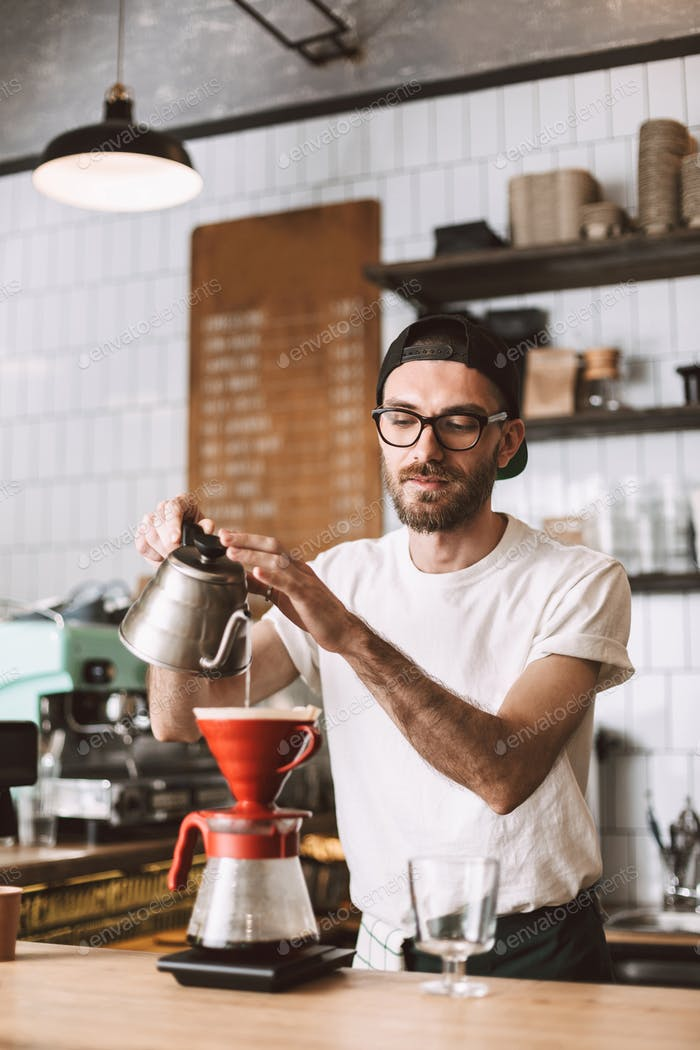 Barista in eyeglasses and cap standing at bar counter and preparing pour over coffee working in cafe