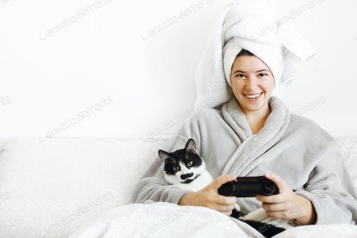 Glückliches Mädchen spielen Video spiele mit Katze im Bett