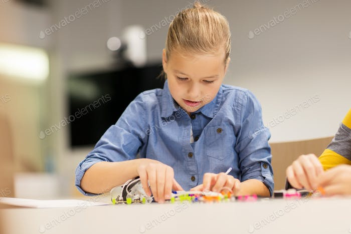 happy girl building robot at robotics school