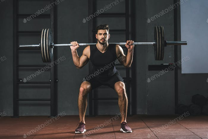 Sportsman doing exercise with barbell on shoulders in gym