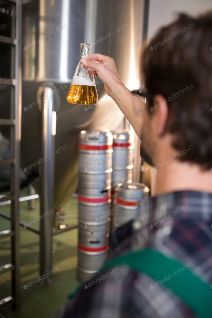 Cropped image of worker examining beer in beaker