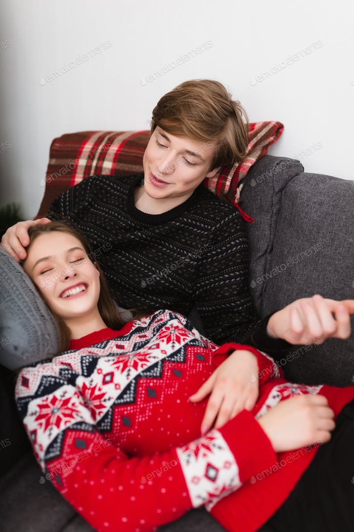 Portrait of beautiful couple lying on sofa at home and happily spending time together