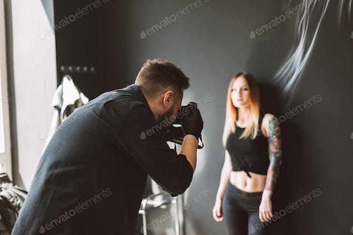 Tattoo master taking photos on camera of tattooed girl standing
