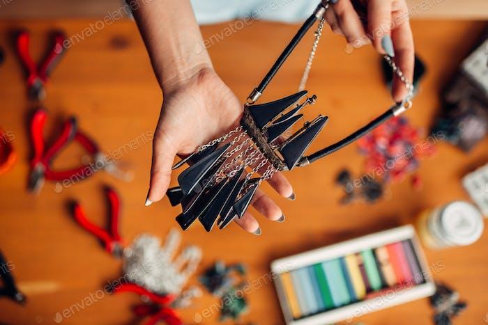 Weibliche Person hält handgemachte Halskette, Handarbeit