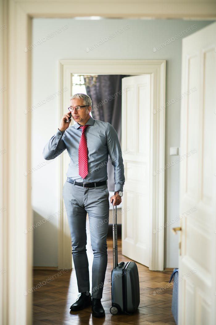 Mature businessman on a business trip standing in a hotel room, using smartphone.