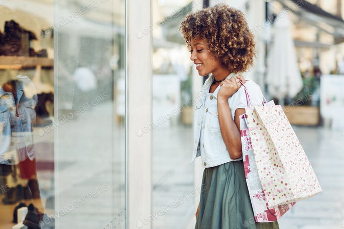 Junge schwarze Frau, Afro-Frisur, Blick auf ein Schaufenster