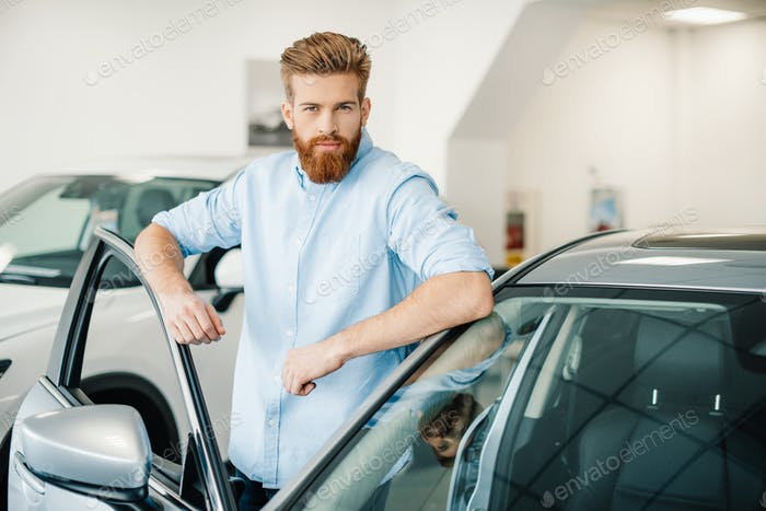 Handsome bearded young man standing with new car in auto salon