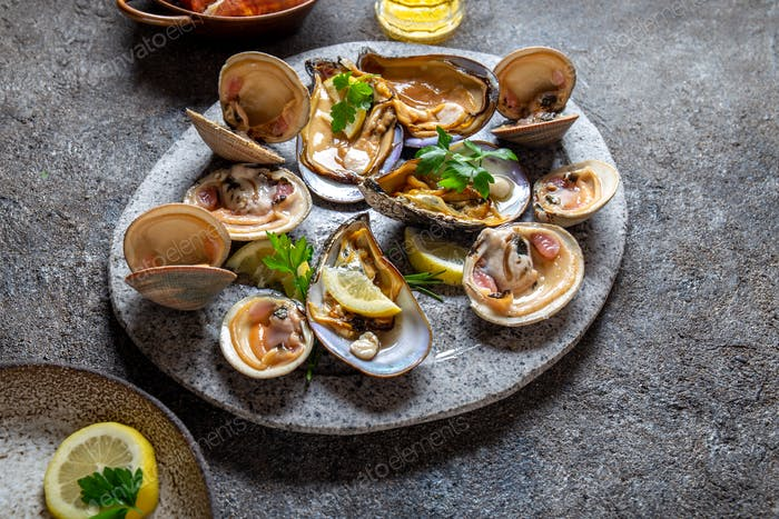Clams amd mussels shell raw fresh seafood on gray plate with lemon.