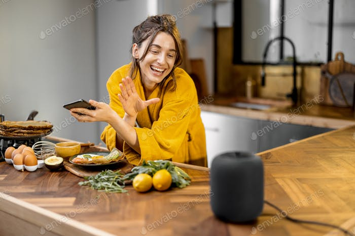 Woman speaking to a smart speaker during a breakfast at home