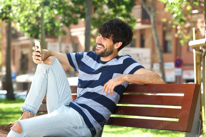 young man smiling with mobile phone in park