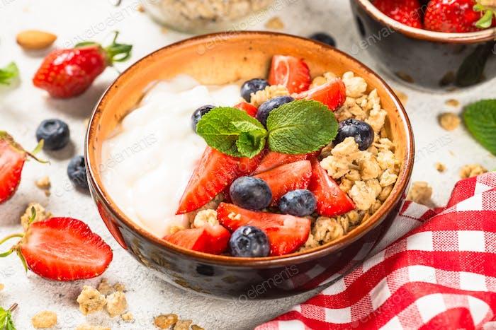Greek yogurt granola with fresh berries on white stone table