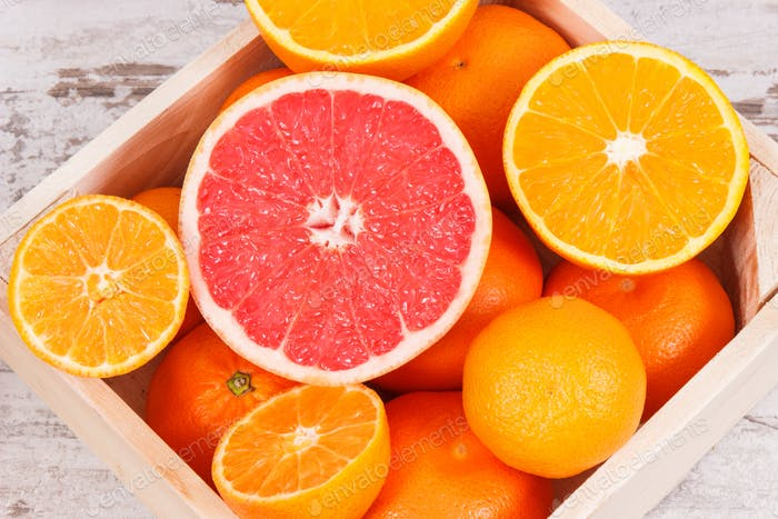 Fresh citrus fruits in wooden box. Slimming, diet and healthy nutrition concept