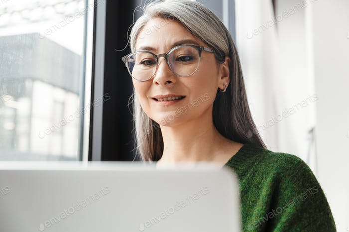 Attractive smiling mature woman with long gray hair standing