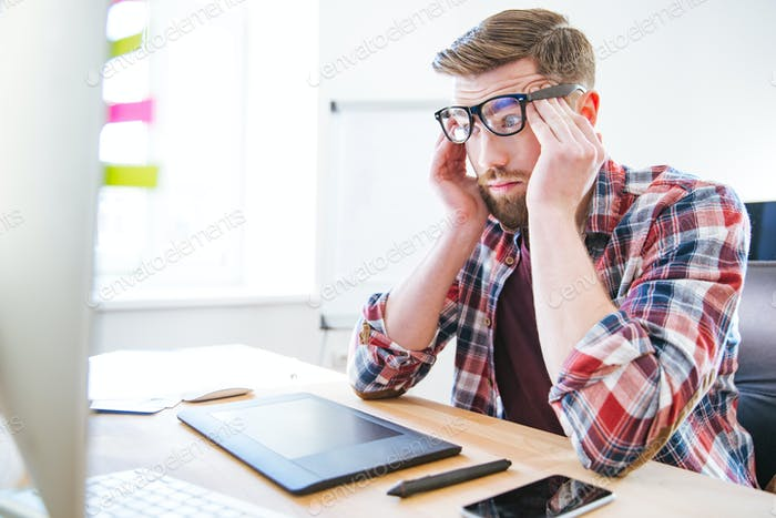 Tired exhausted man sitting on workplace and touching temples