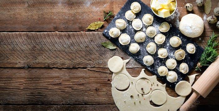 Vorbereitung, Kochen, Herstellung hausgemachter Ravioli, Pelmeni oder Knödel mit Fleisch auf Holztisch Draufsicht