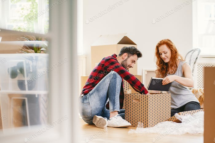 Man and woman unpacking stuff after relocation to new home