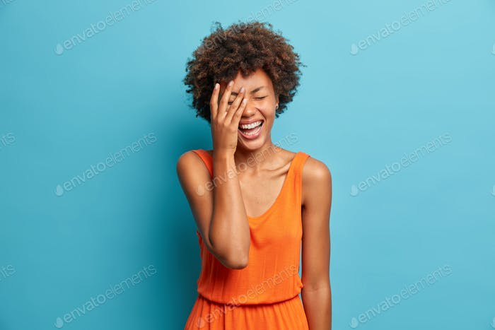 Photo of joyous dark skinned woman makes face palm and smiles broadly dressed in stylish orange dres