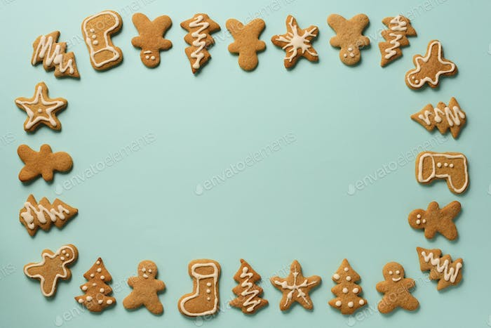 Frame of Christmas gingerbread cookies on blue background with copy space. Pattern of gingerbread