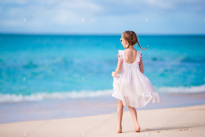 Cute little girl in white dress at beach during caribbean vacation