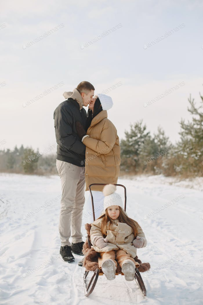 Family in winter clothes play in winter forest
