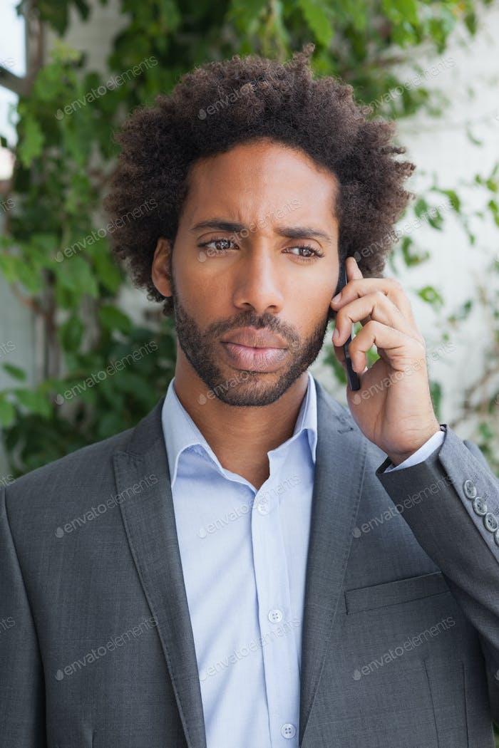 Schöner Geschäftsmann am Telefon an einem sonnigen Tag