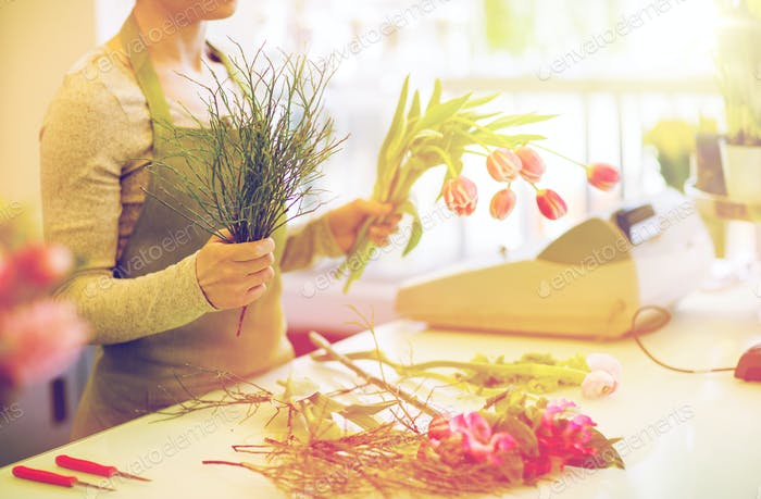 close up of florist making bunch at flower shop