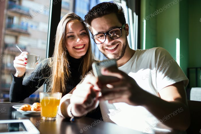 Beautiful young couple having a break time in the coffee.