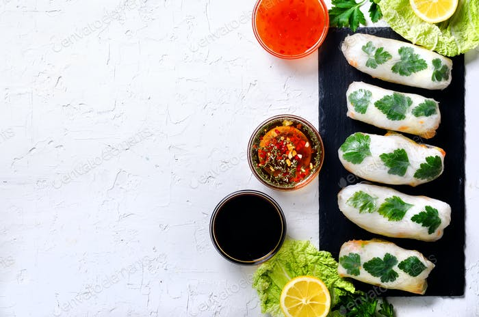 Fresh Vietnamese, Asian, Chinese food frame on white concrete background. Spring rolls rice paper