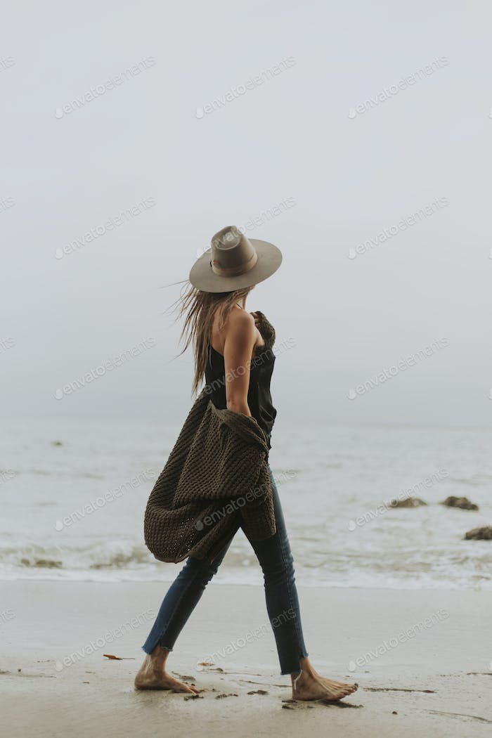 Woman walking barefoot at the beach