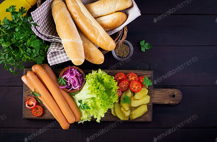 Ingredients for hot dog with  sausage, pickled cucumber, tomatoes, red onions and lettuce