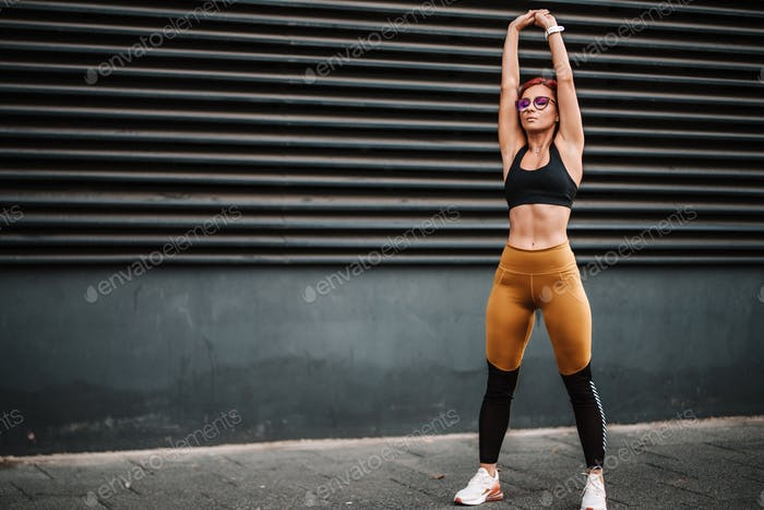 Portrait of fit and sporty sexy woman doing stretching in city urban landscape