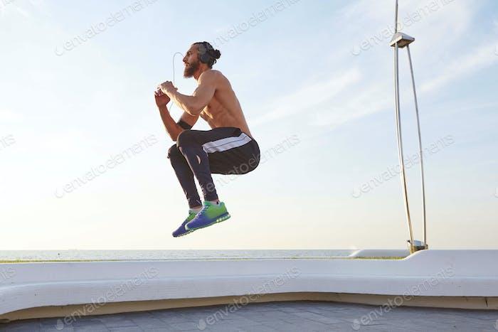 Фото молодого бородатого прыгающего парня с подходящим спортивным телом, выполняющего утренние упражнения имеет мускулистое тело
