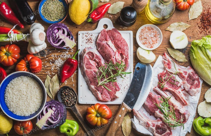 Raw uncooked lamb meat assortment, rice, oil, spices and vegetables