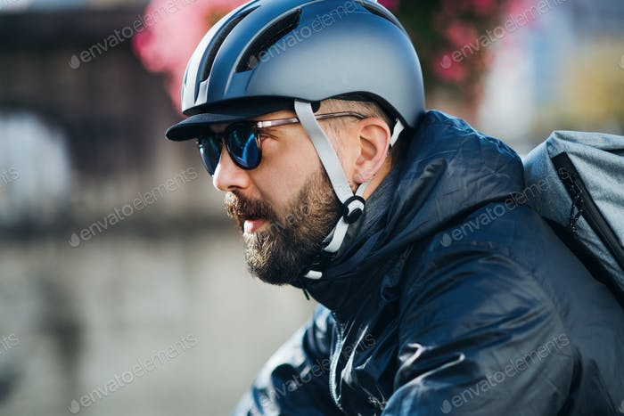 Male courier with bicycle delivering packages in city.