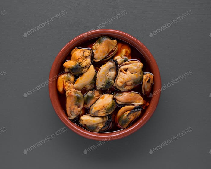 Clay pot filled with mussels in sauce isolated on gray background