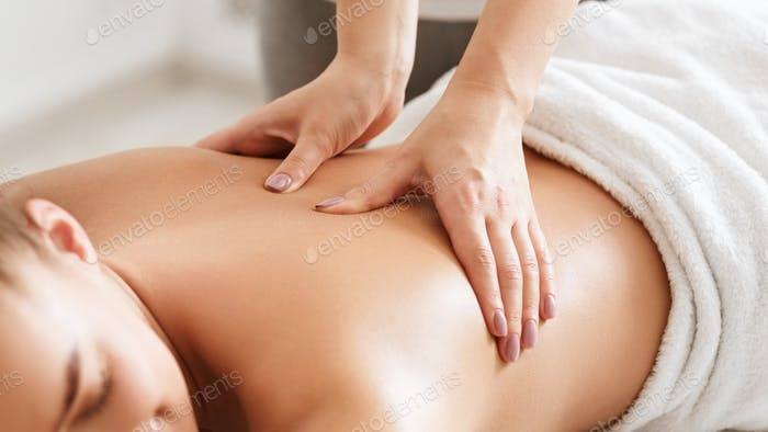 Body care. Young girl having massage, relaxing in spa salon