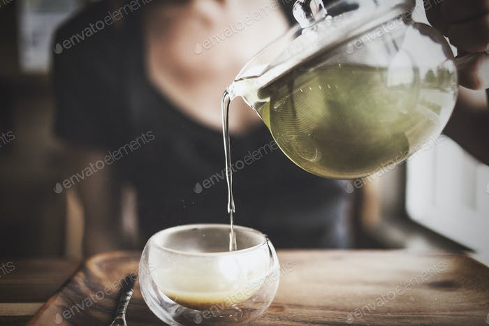 Woman Pouring a Glass of Hot Tea